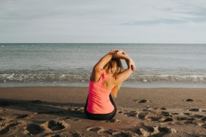 fitness-woman-back-stretching-while-sitting-on-the-sand-at-the-beach_1216-702